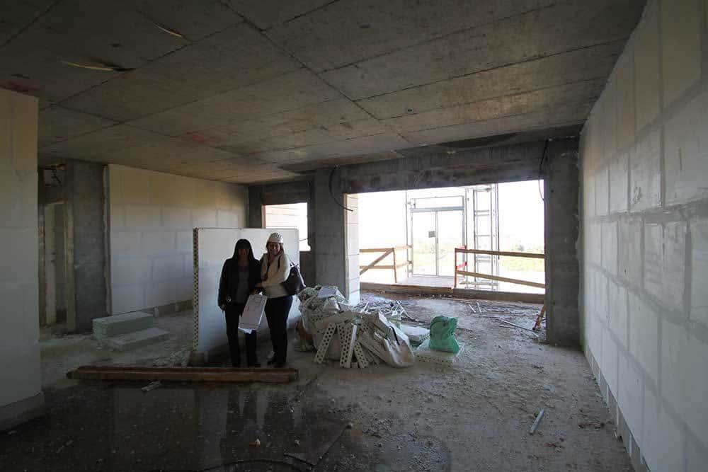 ביקורת באתר הבניה עם לקוחה מרוצה, שינוי מיקום המטבח ומערך הקירות, פתיחת המרחב ויצירת מקומות אחסון.