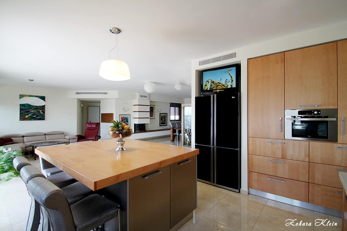 מבט על הדירה והקמין המעוצב מהמטבח